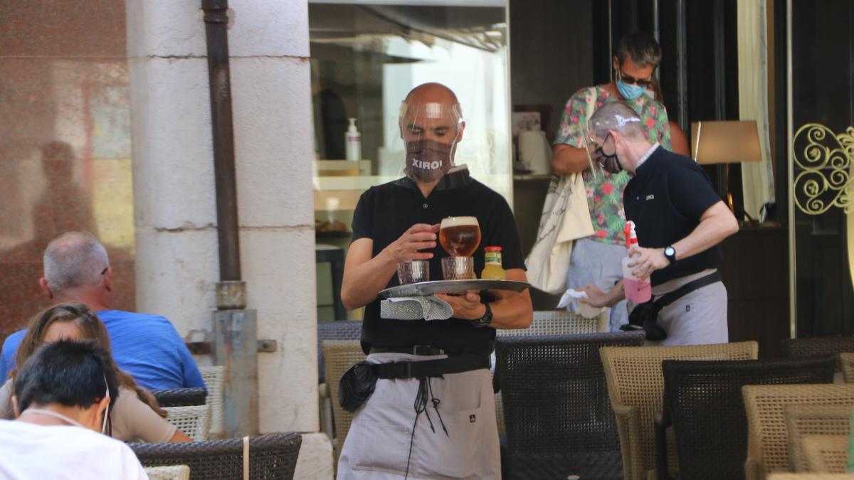 Un camarero atiende en la terraza de un bar de Figueres, este lunes. 03/08/2020