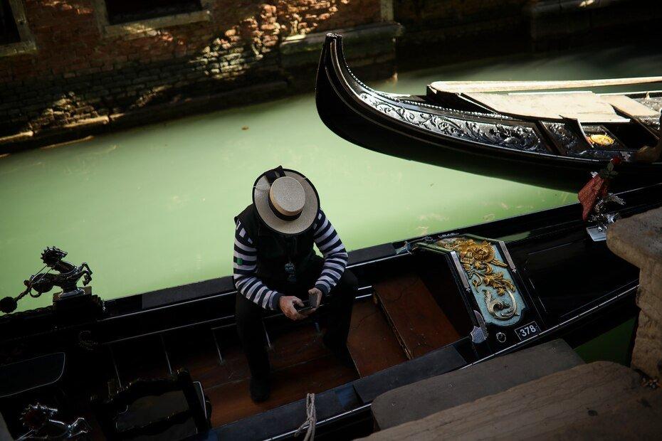 Un gondolero mira su telefono mientras espera ser contratado por alguno de los pocos turistas que visitan Venecia desde el estallido de un brote de coronavirus. Foto del 28 de febrero del 2020.