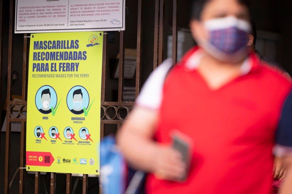 Mellado pasa al lado de un cartel con instrucciones sobre el uso de mascarillas para prevenir contagios en las embarcaciones.