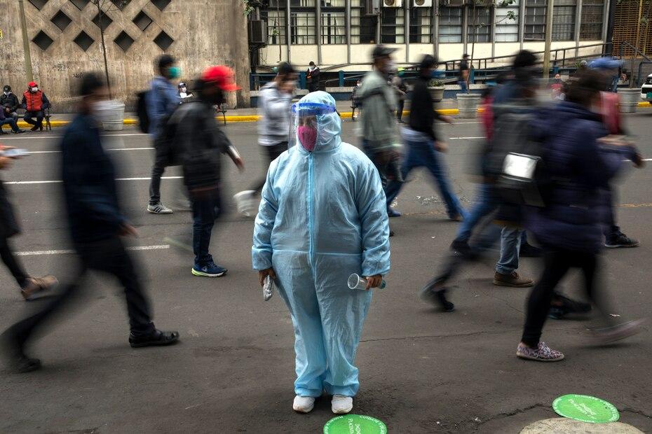 Una mujer espera afuera de una tienda con equipo de proteccion debido a la pandemia de COVID-19 en el centro de Lima, Peru.