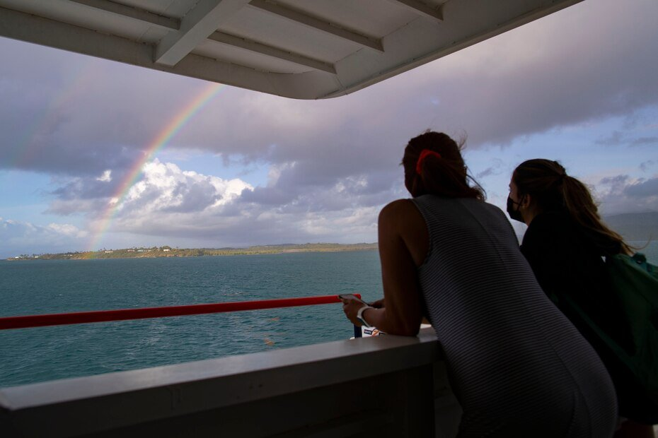 Dos personas observan un arcoiris que se formo mientras se realizaba la travesia hacia Vieques.