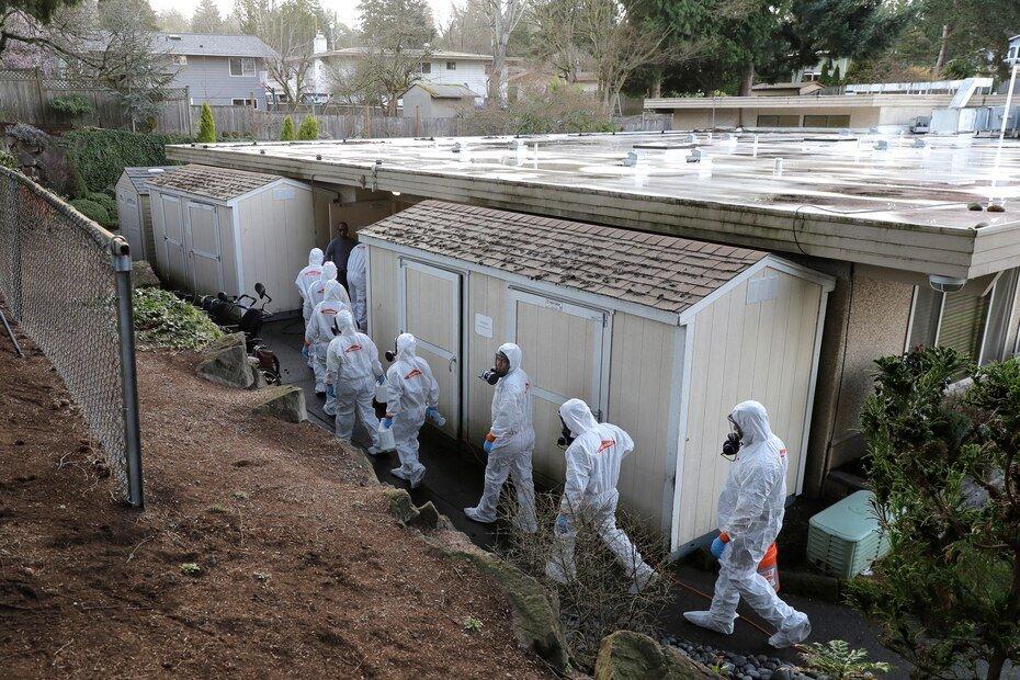 Fotografia de archivo del 11 de marzo de 2020 de empleados con equipos de proteccion, de la cabeza a los pies, se aprestan a desinfectar la casa de ancianos Life Care Center de Kirkland cerca de Seattle, en Washington.
