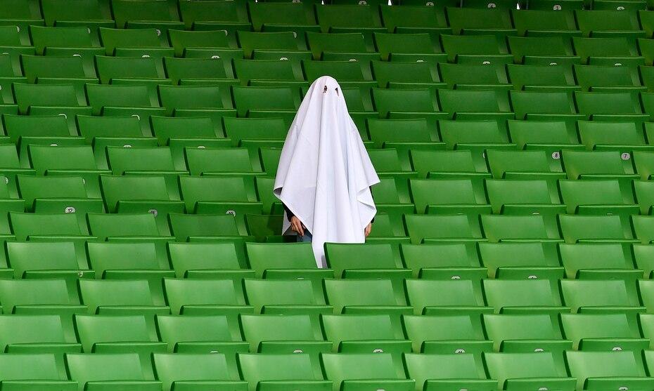 Un hombre vestido como un fantasma de pie en una tribuna vacia antes del partido de ida de los octavos de final de la Liga Europa entre Linzer ASK y Manchester United en Linz, Austria, en esta fotografia de archivo del 12 de marzo de 2020. El partido se jugo en un estadio vacio.