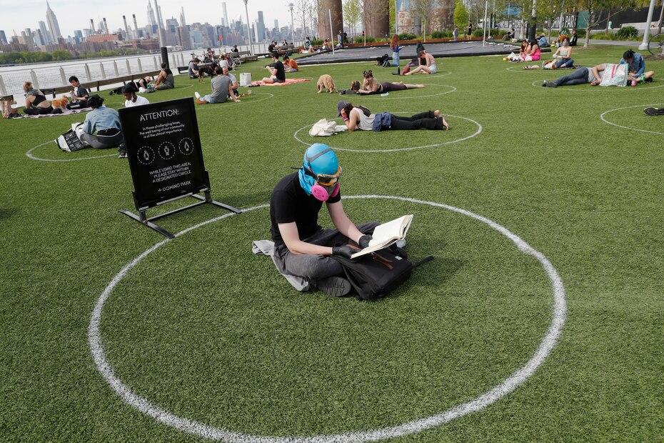 Ridley Goodside usa una cubierta de goma para la cabeza de buceo junto con gafas y una mascara especial de filtracion de aire para protegerse de la propagacion del coronavirus mientras se sienta en un circulo designado marcado en el cesped en el Domino Park de Brooklyn.