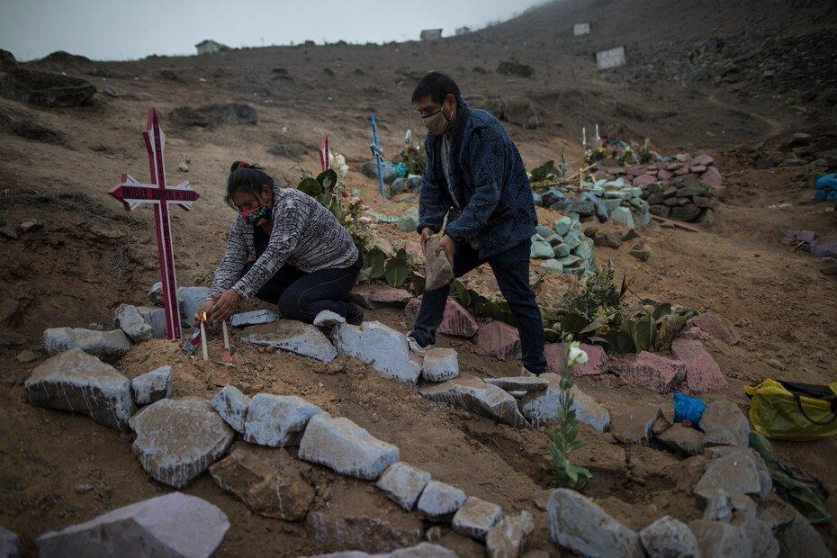 Los hermanos Julia y Jorge Lopez decoran la tumba de su madre, quien recientemente fallecio por el nuevo coronavirus, en un cementerio publico en Lima, Peru, el viernes 22 de mayo de 2020. A pesar de las estrictas medidas para controlar el virus, esta nacion sudamericana de 32 millones se ha convertido en uno de los paises mas afectados por la enfermedad.