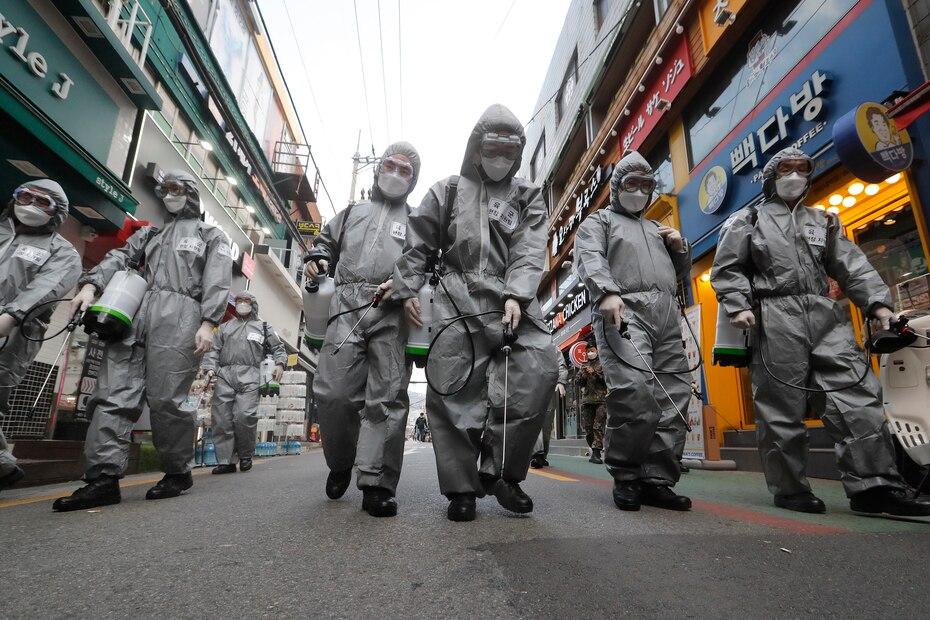 Soldados del ejercito de Corea del Sur con equipo de proteccion rocian desinfectante como precaucion contra el nuevo coronavirus en una calle comercial en Seul, Corea del Sur, el miercoles 4 de marzo de 2020. La epidemia de coronavirus se desplazo cada vez mas hacia el oeste, hacia el Medio Oriente, Europa y Estados Unidos.