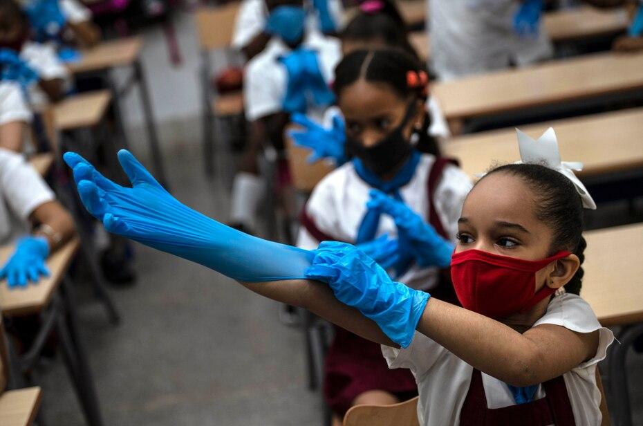 Con una mascara como medida de precaucion en medio de la propagacion del nuevo coronavirus, una niña se pone guantes de plastico durante la clase en La Habana, Cuba, el lunes 2 de noviembre de 2020. Decenas de miles de escolares regresaron a clases en el mes de noviembre en La Habana por primera vez.