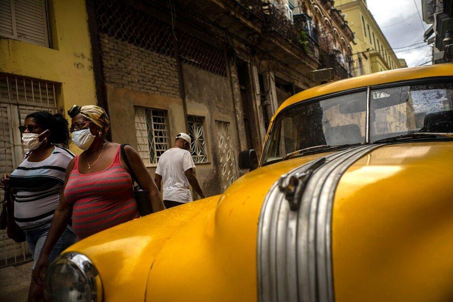 Mujeres con mascaras contra la propagacion del nuevo coronavirus caminan por una calle en La Habana, Cuba, el lunes 25 de mayo de 2020. Las autoridades cubanas exigen el uso de mascaras para cualquier persona fuera de sus hogares