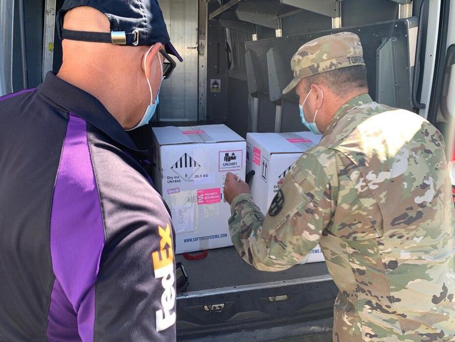 Un empleado de Fedex, la compañia que traslado las vacunas desde Estados Unidos a Puerto Rico, observa a un efectivo de la Guardia Nacional colocar las cajas con las vacunas en la parte trasera de un vehiculo.
