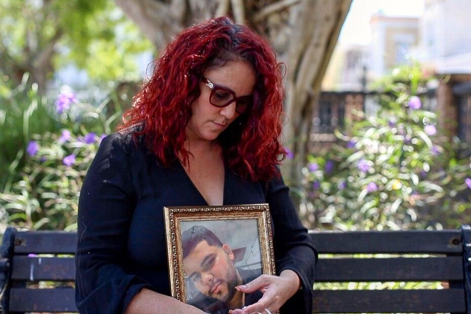 Tras la imposicion de estrictas medidas para contener la propagacion del COVID-19, las familias puertorriqueñas se limitaron a la sepultura de sus familiares sin un velatorio. Directrices del Departamento de Salud prohibieron la aglomeracion de personas para disminuir las probabilidades de contagio. En la foto, Olga Iris Gonzalez sujeta la foto de su hijo muerto por COVID-19, Ramon Francisco Rodriguez.