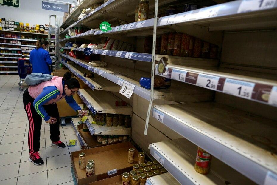 Una compradora sostiene un articulo rodeada de estantes casi vacios en un supermercado en Madrid, en esta fotografia de archivo del 10 de marzo de 2020. La gente hizo compras de panico de alimentos y suministros despues de que el ministro de Salud de España anunciara un fuerte aumento en los casos de coronavirus en la capital nacional y sus alrededores.