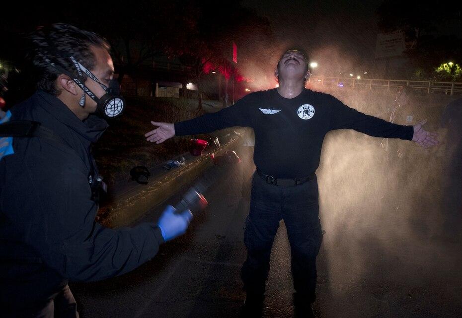 En esta imagen del 30 de mayo de 2020, Óscar Becerril, coordinador de paramedicos, desinfecta a su colega Cesar Ávila despues de salir a recoger a un paciente enfermo de COVID-19 desde su base en Iztapalapa, una demarcacion de la Ciudad de Mexico.