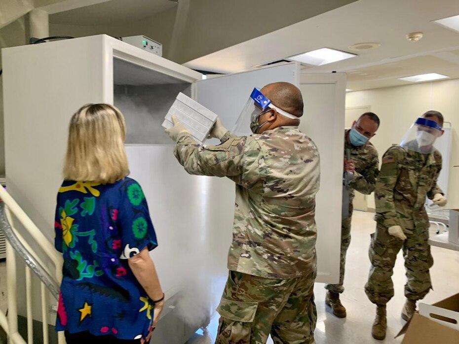 Un efectivo de la Guardia Nacional coloca una caja con vacunas en una de las neveras especiales que pueden almacenarlas.