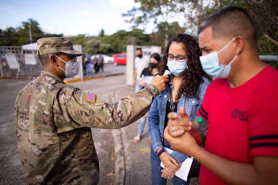 Un soldado de la Guardia Nacional le toma la temperatura a una pareja antes de hacer su entrada a la escuela Maria Simons de Rivera, donde recibirian la vacuna de Moderna.