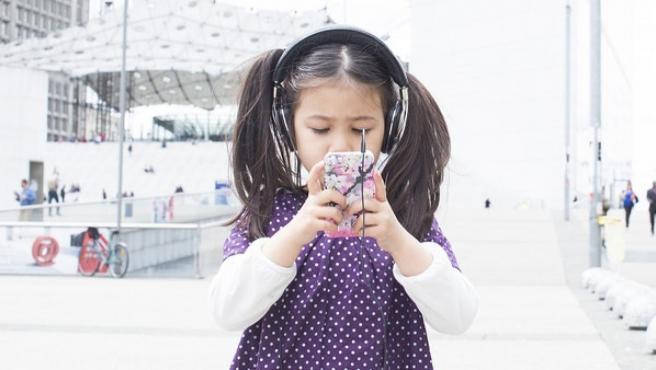 Una niña pequeña con un movil.