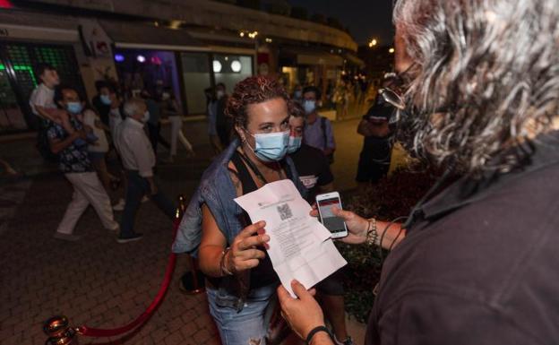 Una mujer muestra un certificado con sus vacunas en regla para acceder a un local en Sansenxo. /EP