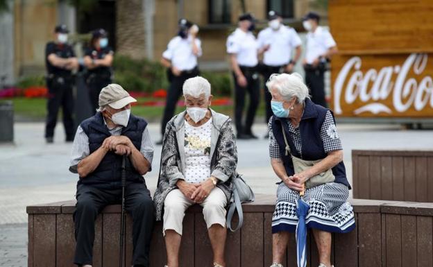 Unos ancianos conversan protegidos con mascarillas. /Efe