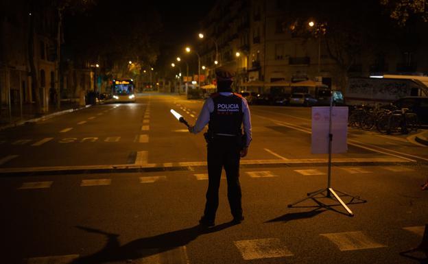 Un mosso colabora en un control durante el toque de queda impuesto en Barcelona. /archivo