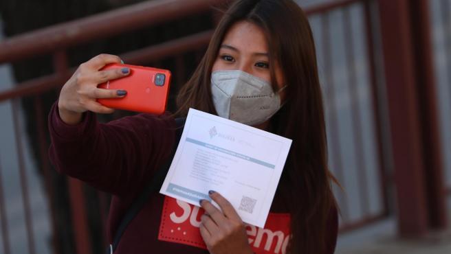 Una joven se hace una foto con su certificado de vacunacion contra la covid-19, en La Paz. Bolivia.