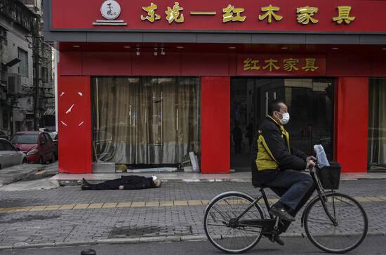 Un ciclista pasa junto al cadaver de un fallecido en Wuhan. /AFP