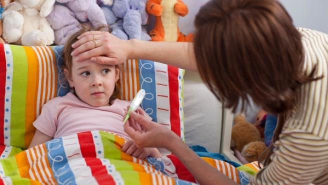 Una madre toma la temperatura a su hija enferma.