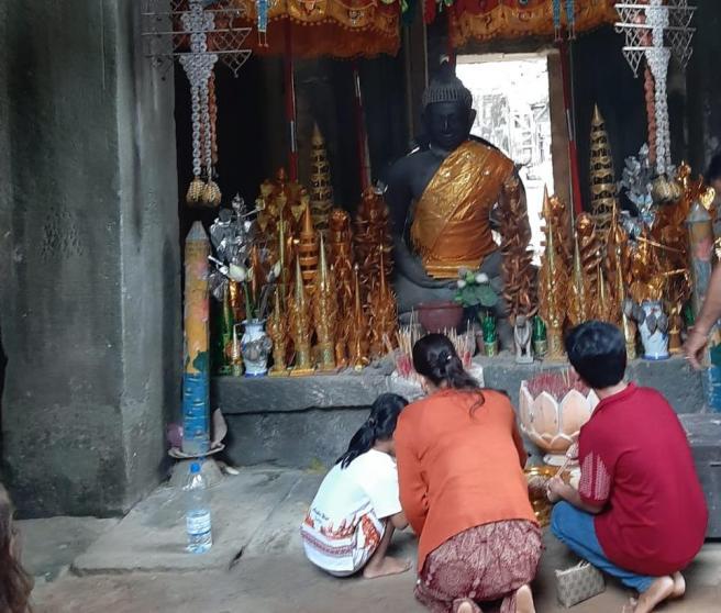 Imagen de archivo de una persona y dos niños rezando en Camboya.
