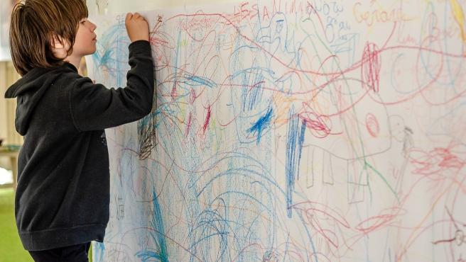 Un niño pintando una pared.