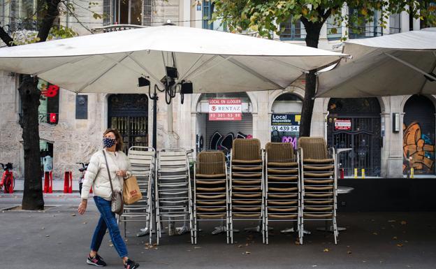 Una mujer pasea ante la terraza de un local hostelero cerrado en el centro de Barcelona./ep