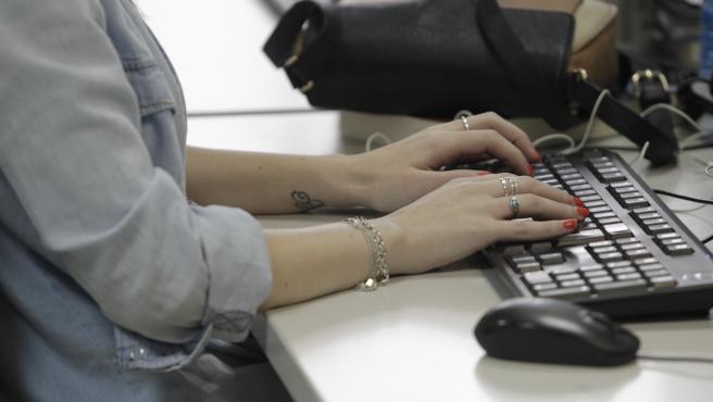 Una trabajadora en su puesto de trabajo en una oficina.